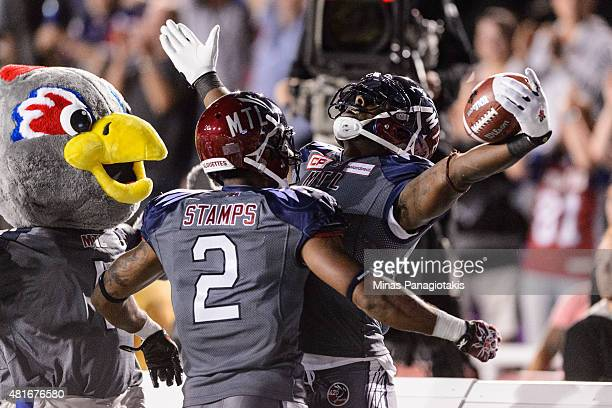 J Green of the Montreal Alouettes celebrates his touchdown with teammate Fred Stamps during the CFL game against the Hamilton TigerCats at Percival...