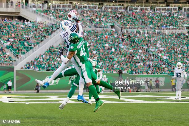 J Green of the Toronto Argonauts makes a leaping catch over Kacy Rodgers II of the Saskatchewan Roughriders for a touchdown in first half action of...