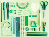 Green office supplies on green background
