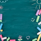 Green old empty chalkboard for copy space with colorful pieces of chalk