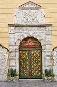 Green old fashioned wooden door on stone facade. Tallinn. Estonia