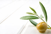 Green olive and branch on white table