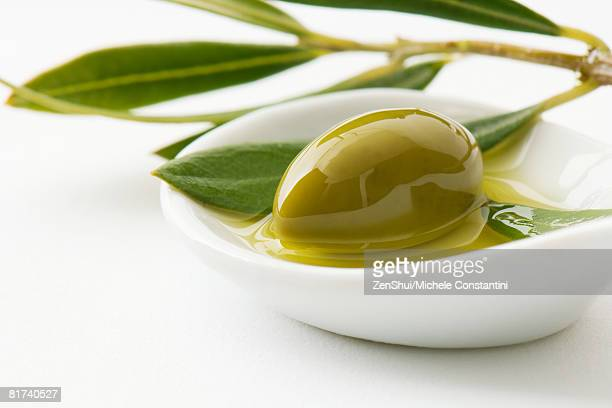 Green olive and sprig of leaves in small dish of olive oil, close-up