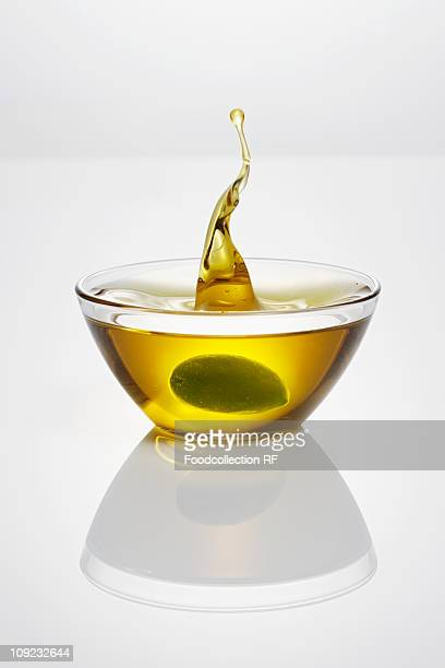 Green olive falling into bowl of olive oil, close-up