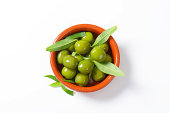 bowl of fresh green olives and leaves on white background