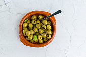 Green Olives in a terracotta dish with light marble background.