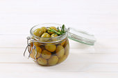 jar of green olives with fresh rosemary on white background