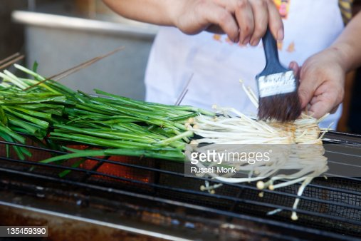 Green onions being basted on a grill