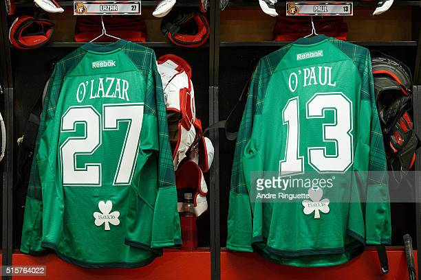 Green Ottawa Senators St Patrick's Day warm up jerseys for Curtis Lazar and Nicholas Paul hang in the locker room prior to the NHL game against the...