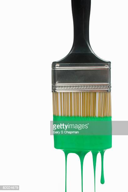 Green paint dripping from brush