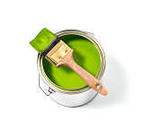 Green paint tin can with brush on top on a white background