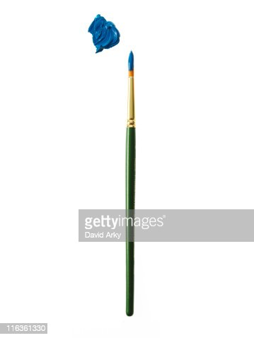 Green paintbrush with blue paint on white background