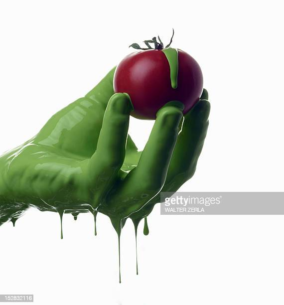Green painted hand holding tomato