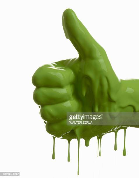 Green painted hand making thumbs-up