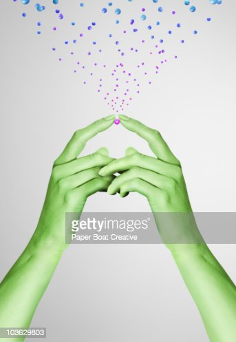 Green painted hands holding a pink metal ball : Stock Photo