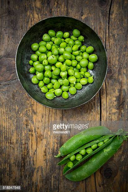 Green peas in a bowl and peapods