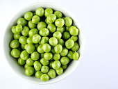 Green peas in the bowl isolated on white background