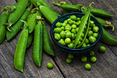 green peas  on rustic white wooden background