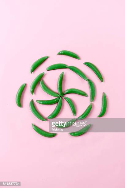 Green peas on pastel pink background. Pastels. Greenery