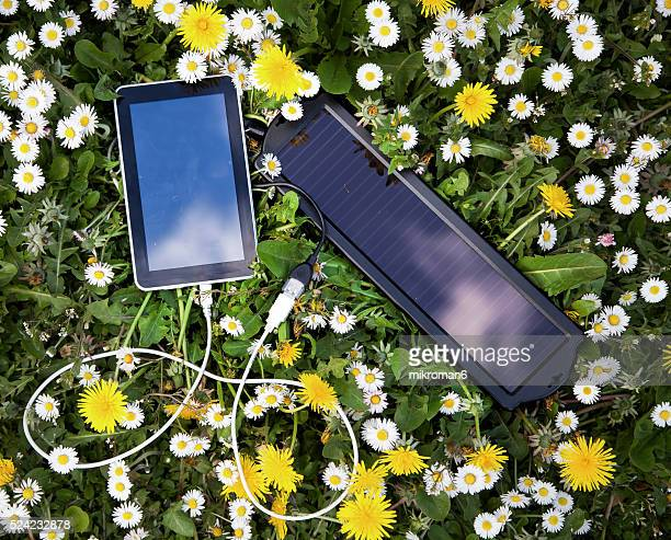 Green power, renewable energy, charging up tablet with solar panel on sunny day .