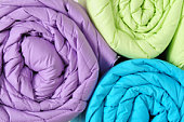 Close up of a colorful rolled up duvets.