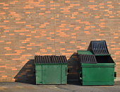 Green recycling dumpsters against a brick wall