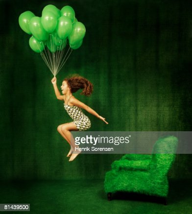 Green room with a girl hanging from a bunch of green balloons. : Stock Photo