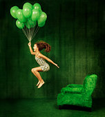 Green room with a girl hanging from a bunch of green balloons.
