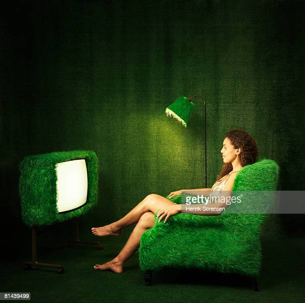 Green room with a turfed television and a woman watching it.