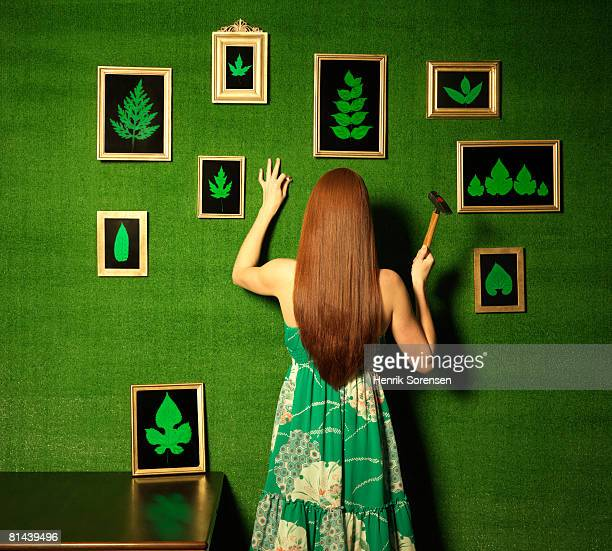 Green room with a woman hanging pictures of leaves on the wall.