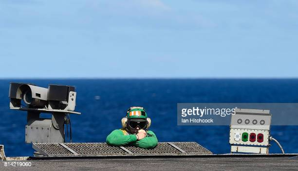 A green shirt 'Hook Runner' crew member looks on before the launch of Super Hornet aircraft on July 14 2017 in Townsville Australia USS Ronald Reagan...