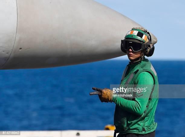A green shirt 'Hook Runner' crew member signals before the launch of Super Hornet aircraft on July 14 2017 in Townsville Australia USS Ronald Reagan...