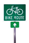 A green sign indicating a bike route ahead silhouetted on a white background