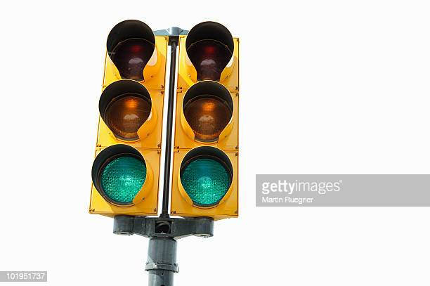 Green signal on traffic light, white background.