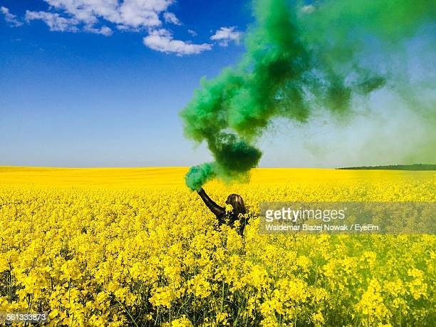 Green Smoke Emitting From Woman Hand Holding Distress Flare On Raps Field