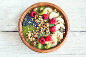 Healthy breakfast green smoothie bowl topped with fruits, nuts, berries and seeds over rustic wooden background