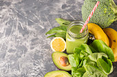 Green smoothie, greens, vegetable and fruits on moody background. Healthy eating, diet and vegetarian concept. Horizontal shot. Copy space for your text.