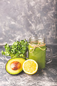 Green smoothie, micro greens, vegetable and fruits on moody background. Healthy eating, diet and vegetarian concept. Horizontal shot. Copy space for your text.