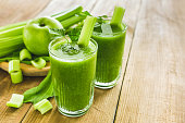 Green smoothie with celery, spinach and apple in two glasses