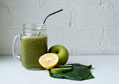Green smoothie in a glass mug with metal straw next to lemon, apple, cucumber and spinach against a white brick wall