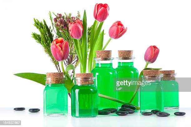 Green soap bottles and flowers isolated on white