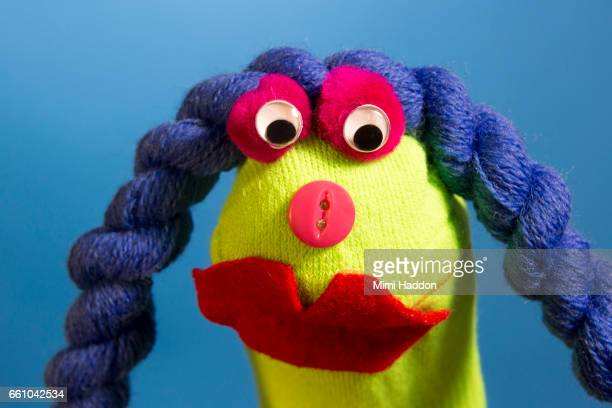 Green Sock Puppet with Big Red Lips Looking into Camera