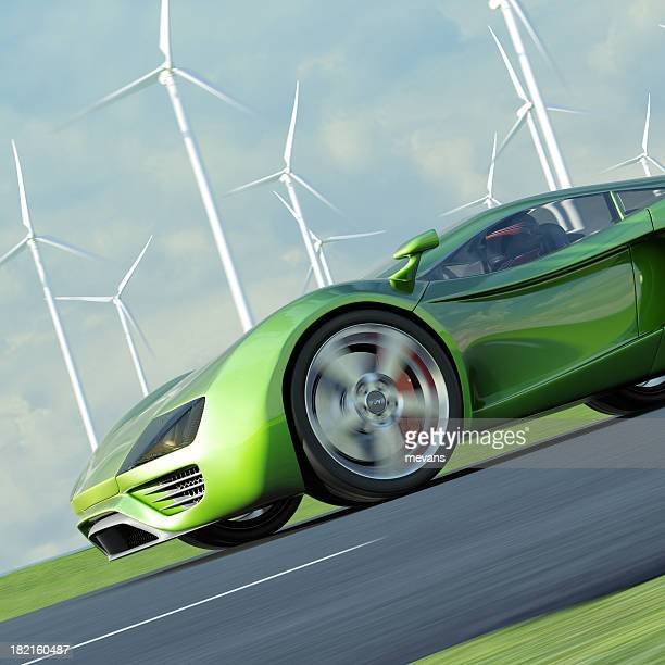 Green sports car driving past multiple windmills