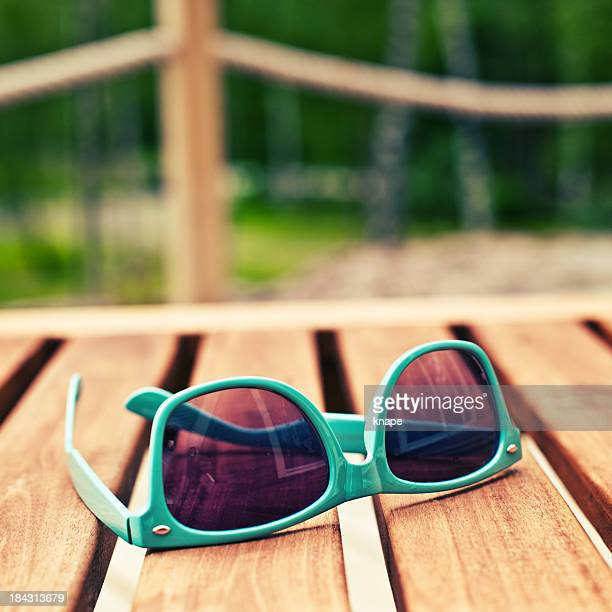 Green sunglasses on outdoor wooden porch