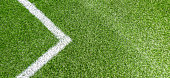 Green synthetic grass soccer football sports field with white corner stripe line. Top view