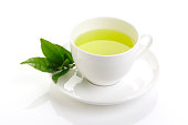 Japanese green tea and fresh green tea leaves on white background
