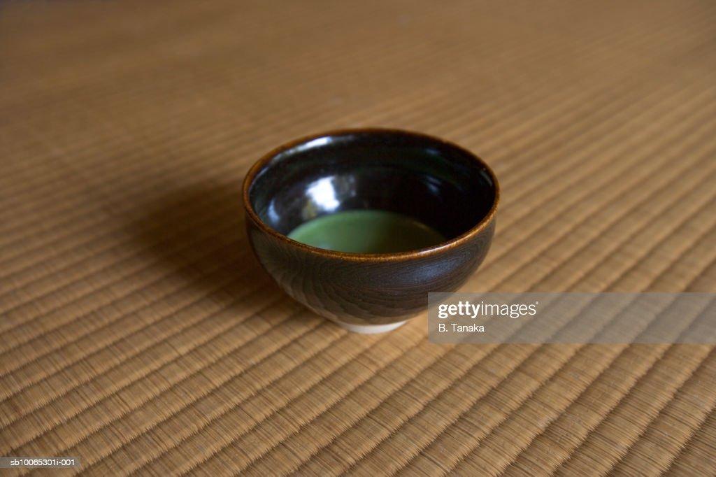 Green tea in bowl on tatami mat, close-up : Stock Photo