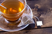 Green tea in a glass teacup on a rustic wooden table