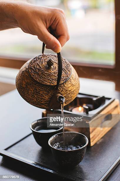 Green tea is being poured in a cup by a man