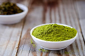 Green tea powder with dried tea in white cup on wooden floor.